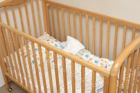 Empty wooden baby cot or crib with colorful pattern linen in the corner of a romom, close up view