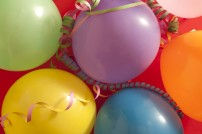 Colourful festive background of multicoloured vibrant party balloons with streamers on a red background for a birthday, carnival or festive holiday celebration